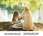 Stock photo little child with labrador retriever dog sitting in sunny summer park near water 340568249