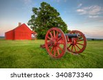 Cannon at Saratoga National Battlefield with Neilson Farm in the background.
