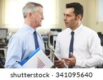 Small photo of Businessman Having Discussion With Senior Mentor In Office