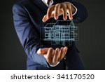 Small photo of Real estate offer. Businessman holds an artificial model of the house