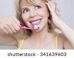 blonde woman brushing teeth | Shutterstock . vector #341639603