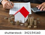 Small photo of Cropped image of businessman calculating tax by model house and stacks of coins on table