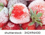 Small photo of Frozen berries. sweet soft red strawberry fruits with a seed-studded surface. Macro view, detailed seeds, achene and ice. Soft focus