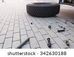 Small photo of Wheel lying on the street, broken mount screw