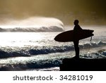 surfer with surfboard looking at waves - stock photo