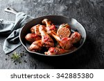 Small photo of Roasted chicken legs in cast iron skillet, selective focus