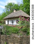 Small photo of Old adobe house under a thatched roof near the lilac bush