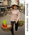 Small photo of Hanoi, Vietnam - October 31, 2015 : A smiling woman in traditional garb sells products from her scales in the Old Quarter of Hanoi, Vietnam on market day