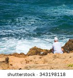 Man Fishing On Rocks By The Sea.