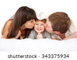 Happy Parents Kissing Child In...