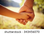 a parent holds the hand of a... | Shutterstock . vector #343456070