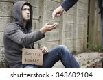 Man Giving Money To Beggar On...