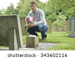 Man Placing Flowers By...