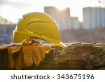 Small photo of yellow plastic helmet for workers security lie on windowsill of window frame against multistories house with construction crane at evening light background Copy space for inscription or objects