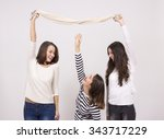 Stock photo short girl trying to reach taller girls scarf 343717229