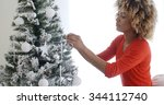 Small photo of Attractive African woman with a wild curly afro hairdo decorating the Christmas tree with tinsel and ornaments to celebrate the festive season