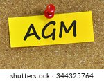 Small photo of AGM word on yellow notepaper with cork background.