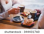 Stock photo coffee and croissants in cafe hands of couple closeup 344431760