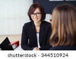 Small photo of Pretty Young Businesswoman Smiling at the Camera While Talking with her Co-worker During a One-on-One Meeting inside the Office.