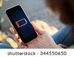 Stock photo close up view of young woman holding a smartphone with low battery on screen all screen graphics 344550650