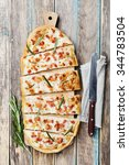 Small photo of Tart Flambe or Flammkuchen on wooden cutting board, traditional Alsatian pie, rustic style, top view