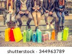 Stock photo group of friends sitting outdoors with shopping bags several people holding smartphones and 344963789