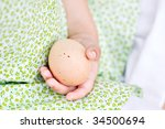 Macro of a little girl's hand as she gathers eggs. - stock photo