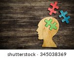 Stock photo human head silhouette with a jigsaw piece cut out on the wooden background mental health symbol 345038369