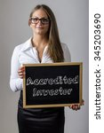 Small photo of Accredited Investor - Young businesswoman holding chalkboard with text - vertical image