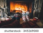 feet in woollen socks by the... | Shutterstock . vector #345269000