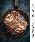 Small photo of Roasted veal shank slices in frying pan on rustic background, top view, close up