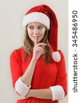 Small photo of modesty girl in santa showing the silence sing. Christmas and New Year concept
