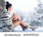Small photo of Young beautiful happy brunette woman drinking cup of coffee wearing knitted nordic print poncho sitting home by the window. Blurred winter snow tree background