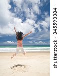 asian girl jumping on beach on... | Shutterstock . vector #345593384