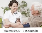 smiling young nurse taking old... | Shutterstock . vector #345680588