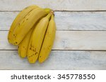 some bananas on a white wooden... | Shutterstock . vector #345778550