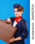 Small photo of Stewardess with face art holds suitcase. Young attractive girl in a blue suit flight attendants. Airfreight. Service. Baggage.