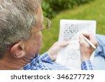 Stock photo senior man doing crossword puzzle in garden 346277729