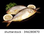 Small photo of Two amberjack with two lemon wedges and parsley on black