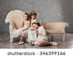 Two Little Girls Sitting On A...