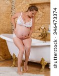Small photo of Pregnant woman with abdominal pain in the bathroom of the house. Premature birth, labor pains.