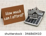 Small photo of Home Mortgage Affordability, A gray house, brown card and calculator on stone background with text How much can I afford