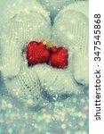 hands in woolen mittens holding ...   Shutterstock . vector #347545868