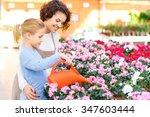Watering Plants. Little Girl...