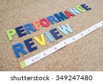 """Small photo of Word spelling """"Performance Review"""" and measuring tape on cork board"""