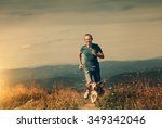 Stock photo man running with his dog on the mountain tableland 349342046