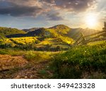 wooden fence in the grass on the hillside near the village in evening light - stock photo
