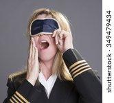 Small photo of Sleepy aircrew officer yawning and using an eye shade