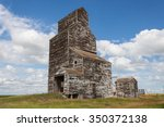 Old Wooden Grain Elevator with Blue Sky and Clouds - stock photo