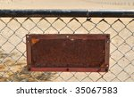 Rusty old sign on a fence with space for text - stock photo